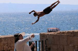 A woman taking a selfie while a young man dives off a wall into water.