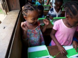 أطفال داخل فصل دراسي وأمامهم أجهزة صغيرة