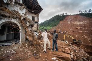 ألفريد جوني يتحدث إلى صديقه أمام منزل مدمر بسبب الفيضانات