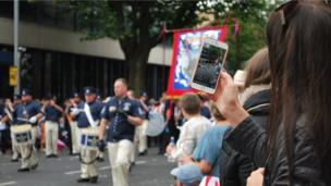 Girl uses phone to film Twelfth of July parade in Belfast
