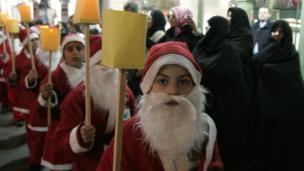 Noel baba kostümü giymiş çocuklar Şam'daki karnavalda yürüyorlar