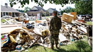 "Chris Daves, a National Guardsman, surveys the damage from a friend's yard. He's there to help and listen, ""We're fellow Army men, that's what we do."" Watson, LA."