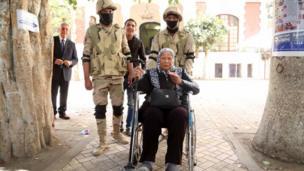جنود يدفعون كرسي متحرك تجلس عليه امرأة مسنة