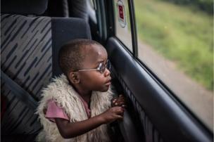 Na viagem de retorno ao povoado natal de Bundibugyo, Criscent olha pela janela do carro com surpresa.
