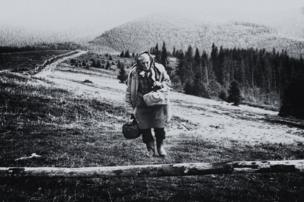 An elderly woman walks down a path.