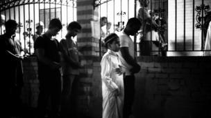 Niño rezando durante el Ramadán en la calle fuera de la mezquita porque la mezquita está llena, Parkchester Jame Masjid, en el Bronx, 2012.