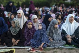 Palestinian Muslims attend the Eid al-Fitr prayer in an open area of Gaza City, 25 June