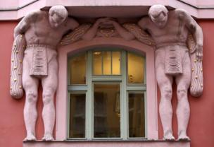 Two sculptures of men support a building