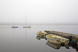 A misty lake with two boats tied to a shore