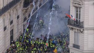 Protesters flee as the police in Paris fire tear gas