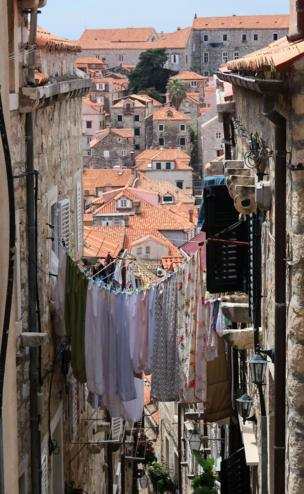 A narrow street connected by a washing line full of clothes over looks a town in the distance