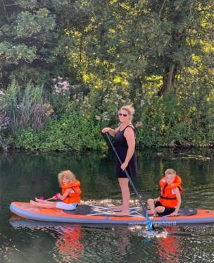 Woman and children paddle boarding