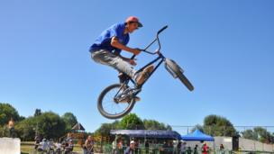 Un adolescente en el aire con su bicicleta y el cielo azul en un parque en Osorno