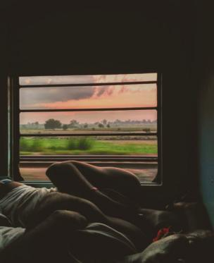 Two men sleep next to each other on a lower berth.