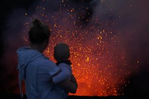 A mother holds her baby in front of a volcano