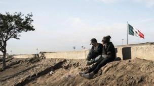 सफ़र शुरू करने के पहले मेक्सिको की सीमा के पार बैठ लोग