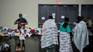 Flood victims in Red Cross blankets look for clothing at a shelter in the George R. Brown Convention Center