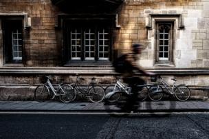 A cyclist passes a building
