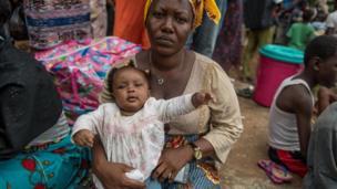 كادياتو جالسة وطفلتها في حجرها بانتظار المعونة الإغاثية