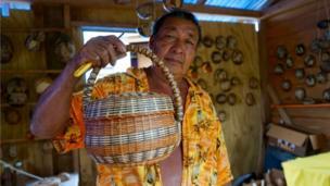 Willard Bruney shows off a basked a has woven