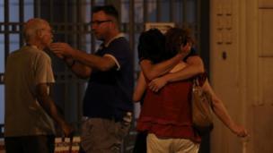 Unas personas se abrazan en una calle de Niza.