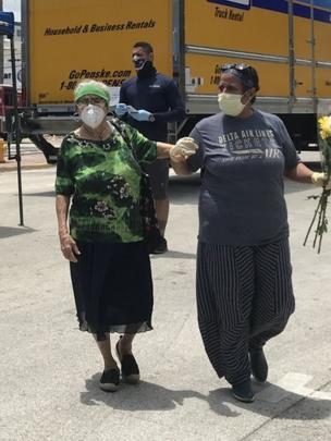 Una voluntaria ayuda a una mujer a acercarse a la acera