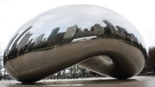 Reflejos de los edificios en una escultura de metal