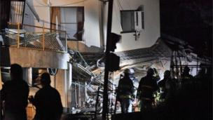 Firefighters search for trapped residents at a collapsed house in Mashiki, near Kumamoto city, southern Japan, after the earthquake early Friday, April 15, 2016.