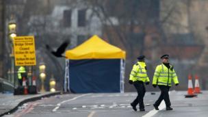 Police officers walk across Westminster Bridge
