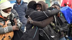 Des migrants se disent au revoir dans le sourire avant de quitter le camp de Calais.