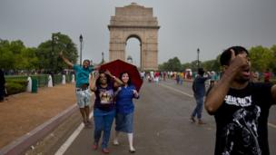 Indians enjoy a sudden rain and thunderstorm at the India Gate in New Delhi, India, Monday, May 23, 2016.