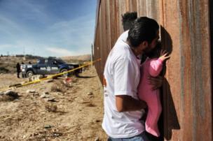 رجل يحمل رضيعا على الجدار الحدودي بين المكسيك وأمريكا