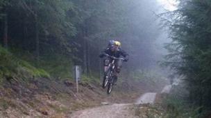 A rider lifts off along a trail at Llandegla mountain biking centre