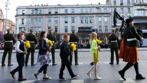 Children carry daffodils outside the GPO in Dublin as part of the Easter Rising centenary commemorations