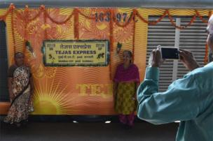 In this photograph taken on May 22, 2017, Indian passengers pose for a photograph alongside the Tejas Express luxury train during its first journey between Mumbai and Goa at Ratnagiri