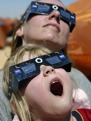 Niña y mujer viendo eclipse sorprendidas.