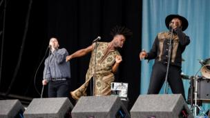 The band members of Young Fathers onstage