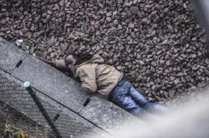 A man hides on the railway tracks trying to avoid detection from the French police. He was trying to make his way to England via the Channel Tunnel in Calais, France.