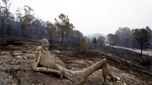A burnt sculpture is seen after a forest fire in As Neves, Galicia, Spain, near the border with Portugal, 1