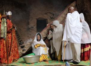 Baptism in a church in Lalibela, priests presiding on the left