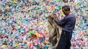 Chinese worker sorts all up in plastic bottles