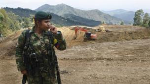 A female Farc rebel stands at a transition zone where diggers are still at work