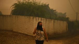 Una mujer se cubre la boca y la nariz para protegerse del humo en la aldea de Torgal, Castanheira de Pera, el 18 de junio de 2017.
