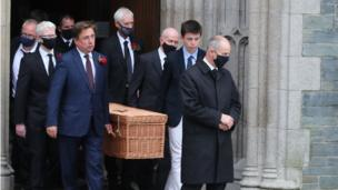 The casket of the former SDLP leader is carried by his son, John Hume Junior, and other family members.
