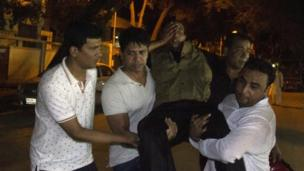 People carry an injured man near the Holey Artisan Bakery restaurant in Dhaka