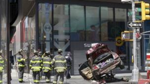 Firefighters look on at a crashed car in New York
