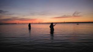 Two men lave netting for salmon near the Second Severn Crossing at daybreak