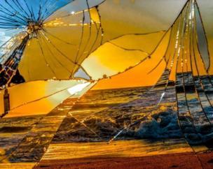 A broken mirror reflects the sun setting over the sea.