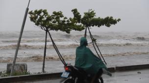 Một người dân đi xe máy trên bờ biển huyện Diễn Châu, tỉnh Hà Tĩnh trước khi bão Doksuri đổ bộ. Bão Doksuri được cho là cơn bão mạnh nhất vào Việt Nam trong một thập kỷ qua.