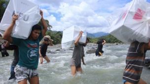 Nehirden geçerek çuval taşıyanlar